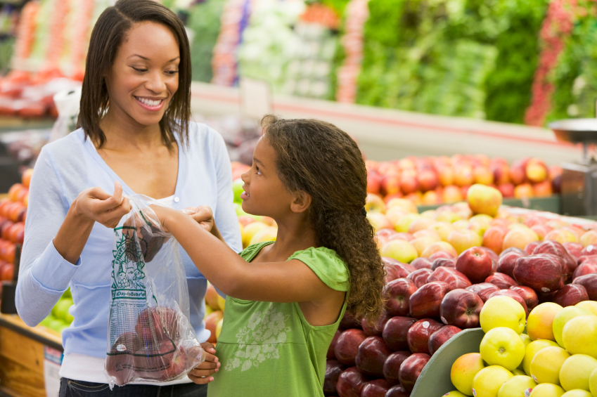African American Mother and Daughter in produce section of grocery store
